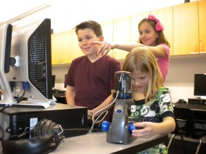 Mellanstadiebarn studerar ett material med ett USB-mikroskop. Bild av Brad Flickinger.