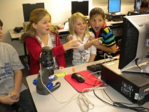Några barn leker med ett USB-mikroskop, direktanslutet till en dator. Bild av Brad Flickinger.